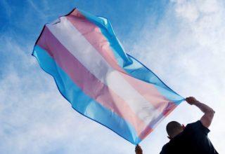 Pessoa segurando bandeira que representa a comunidade trans