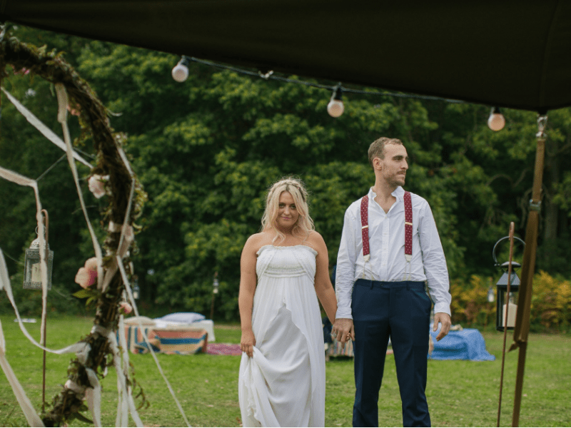 Image of bride and groom, Clemmie and Max, standing in front of their Giant Tipis with the woods in the background.