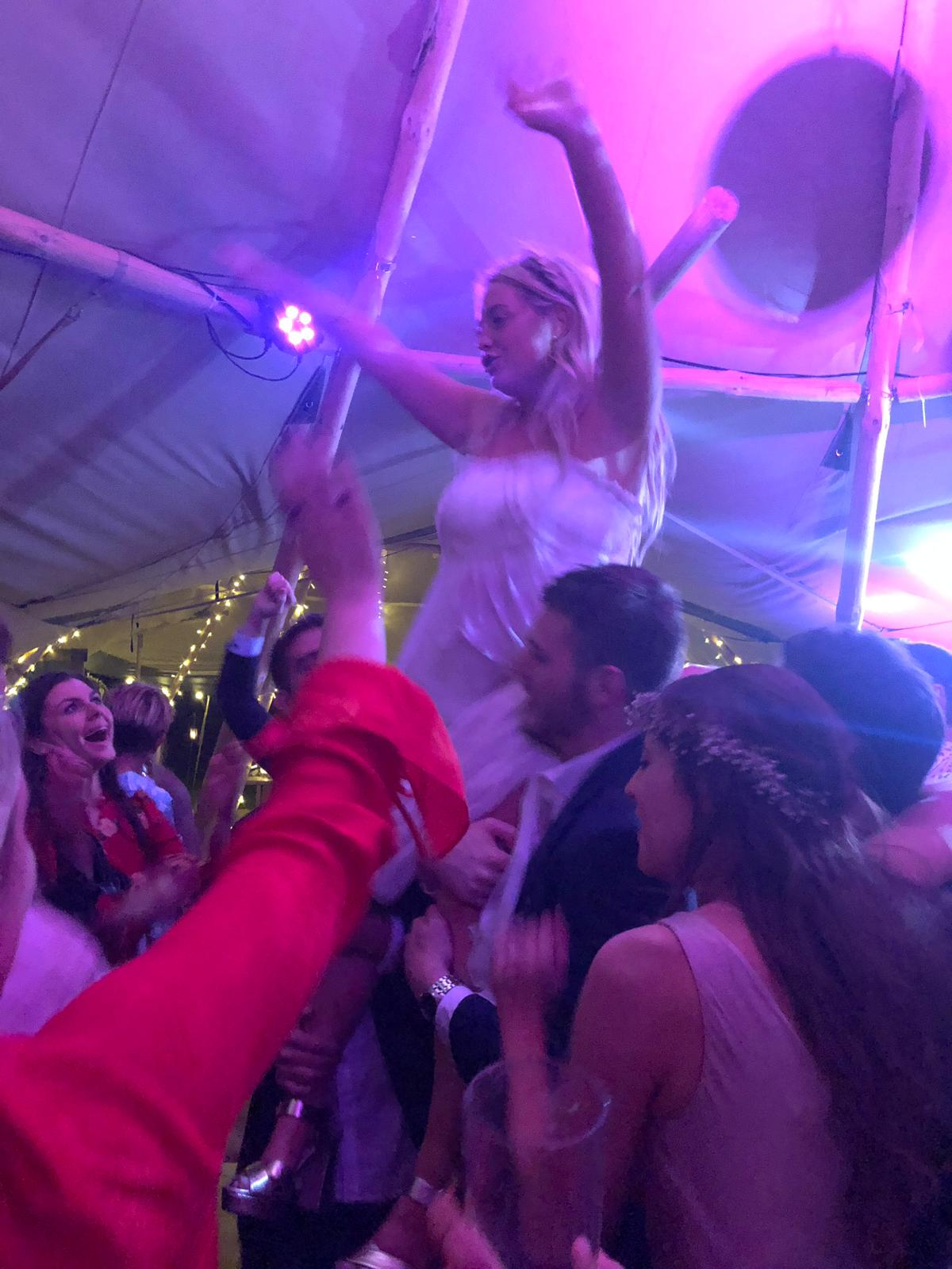 Bride partying at her tipi wedding. Coloured uplights add to effect