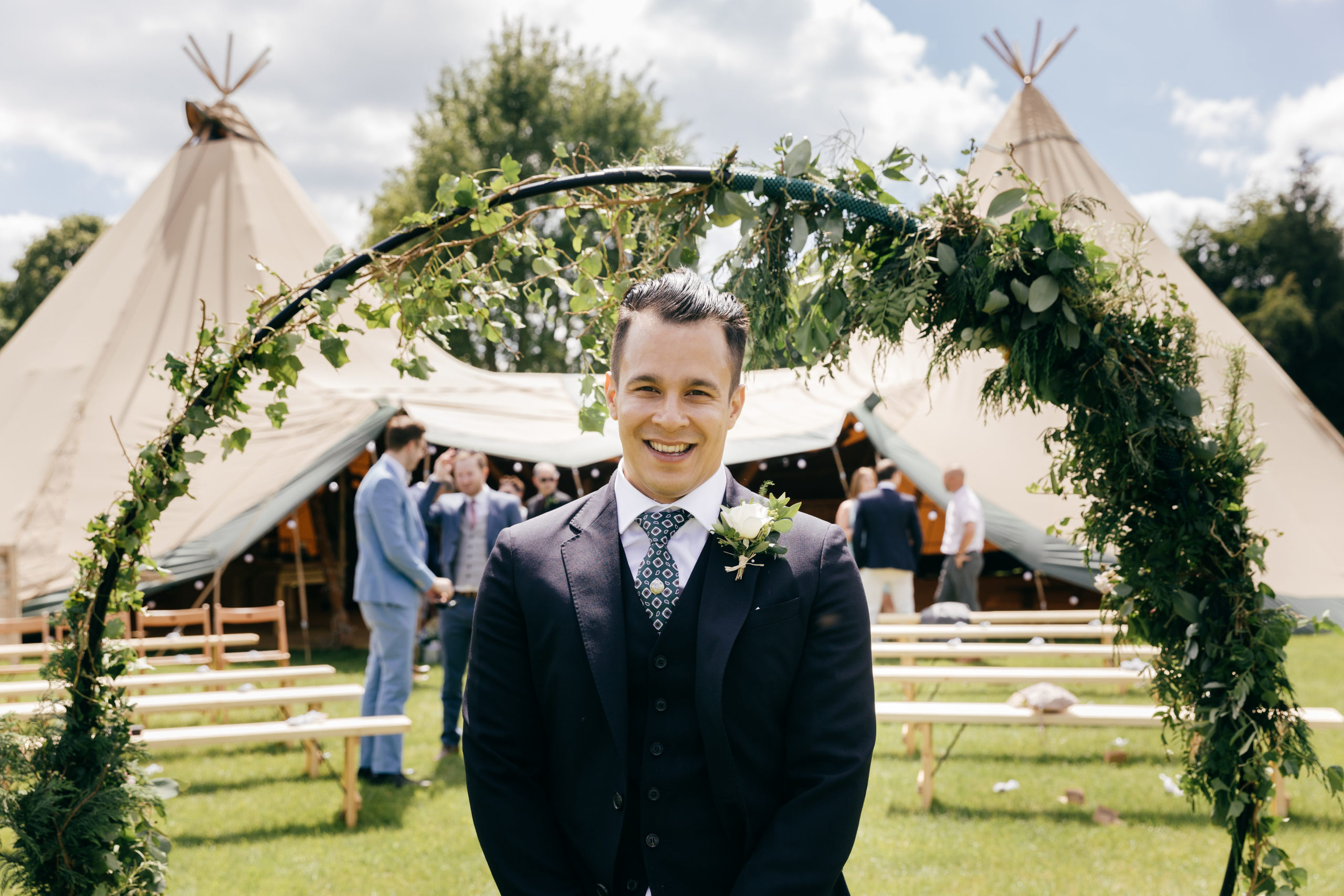 Groom Hassan before ceremony at Cotswold Tipis Wedding with ivy entwined circular ceremony feature