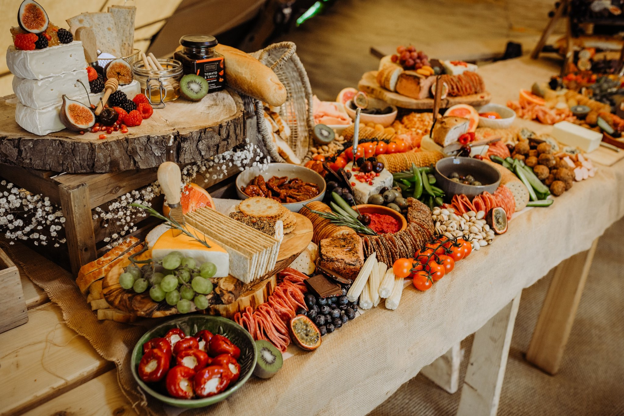A fully packed Grazing Table by Wild & Brie catering, including breads, crackers, cheese. fruit and vegetable sticks, dips, antipasti, pork pies and pate