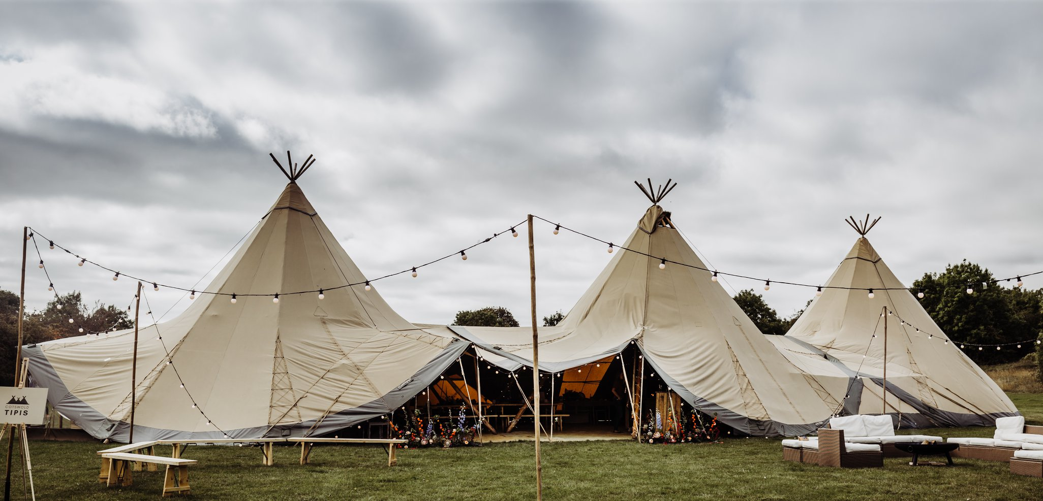 Three connected tipis with central entrance, outdoor seating area with fire pit to the right and ceremony area to the left.