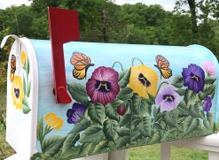hand painted mailbox with colorful pansies and butterflies
