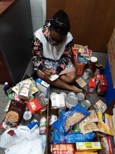 Student doing inventory on donations to the Cottey Cupboard