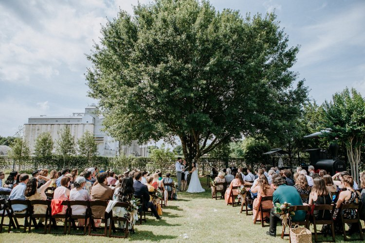 A couple gets married under a tree with their guests looking on.