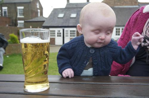 un bébé qui a l'air saoul accompagné d'une grosse pinte de bière
