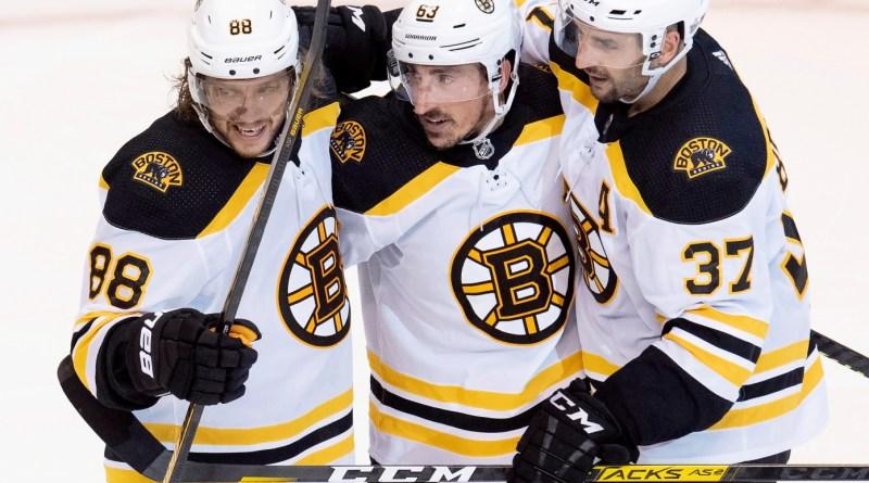 Bruins' players David Pastrnak, Brad Marchand, and Patrice Bergeron celebrating a goal.