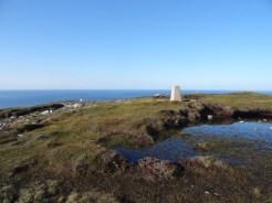 Trig point on Dùnan Mòr, lighthouse in background.