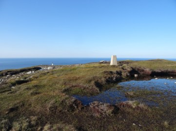 Trig point on Dùnan Mòr, lighthouse in background.