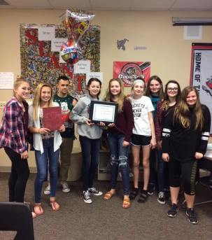 SeAnna Brennan, Jaden Miner, Adviser Jason Davis, Brooke Wine, Chloe Krueger, Madonna Parker, Megan Ash, Hannah Molino, and Rheanna Allison collect their award after earning second place in the Lifetouch National Yearbook Showcase.
