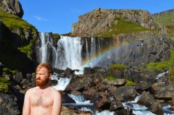 Half naked Daan in front of a waterfall with a rainbow   Gay Couple Road Trip East Iceland © Coupleofmen.com