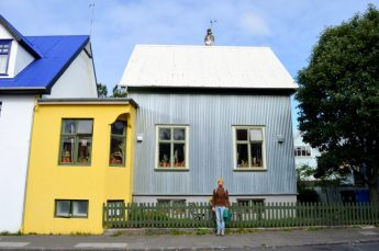 Reykjavik Gay Travel Daan in front of a grey and yellow house   Gay Couple Travel City Weekend Reykjavik Iceland © Coupleofmen.com