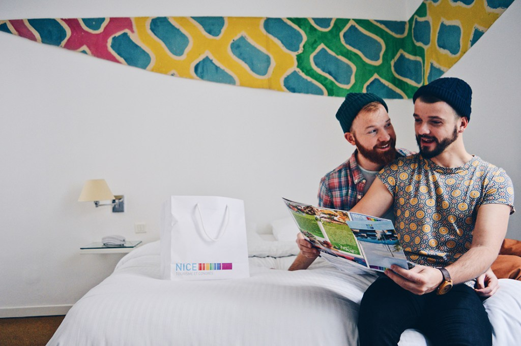 Gay Couple City Weekend Nice - two gay guys on a bed planning city trip in France