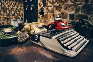 "A green, red, and white telephone and a type writer at Escape Room ""Bunker"" from Fox in a Box © CoupleofMen.com"