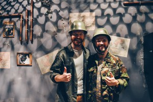 "two gay guys in army clothes after winning the Escape Room ""Bunker"" from Fox in a Box © CoupleofMen.com"