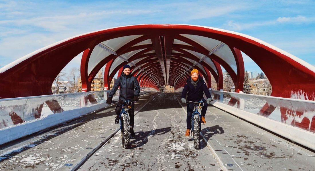 Karl & Daan in front of the red Peace Bridge by Calatrava | Fat Tire Biking Calgary Nomadic Mobile Gear © CoupleofMen.com