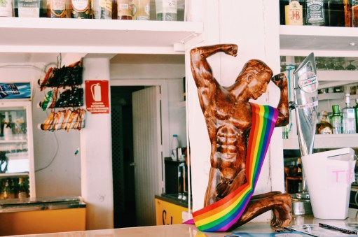 Gay Travel Ibiza Six Pack with Rainbow Flag at Chiringay | Gay Couple Travel Gay Beach Ibiza Town Spain © CoupleofMen.com