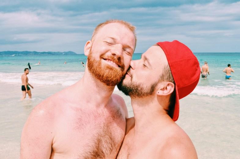 Gay Travel Ibiza Spartacus Gay Travel Index 2018 Karl & Daan kissing at the Beach | Gay Couple Travel Ibiza Gay Beach The Cruise Spain © CoupleofMen.com