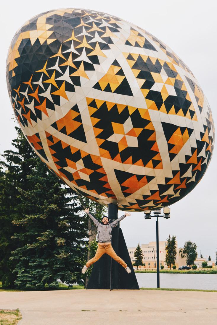 Karl Jumps infront of the giant sculpture of a pysanka, an Ukrainian Easter Egg at Vegreville | Road Trip Edmonton Northern Alberta © Coupleofmen.com