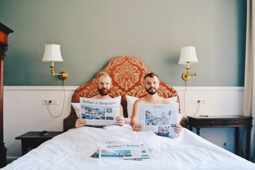 Gay-friendly Hotel Berlin Henri Kurfürstendamm Charlottenburg Gay Couple naked in bed reading Berliner Morgenpost Newspaper about Gay Pride © Coupleofmen