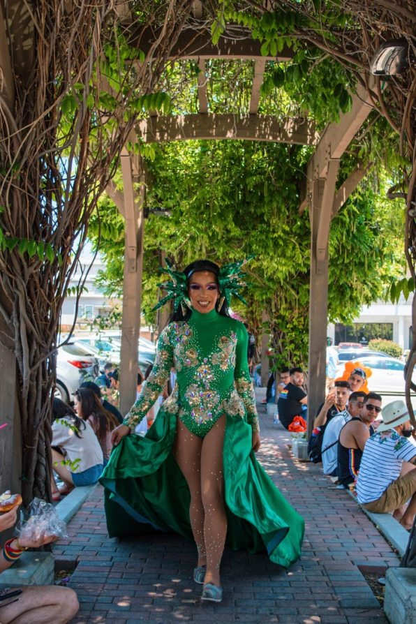 Even during lunch break - Drag Beauty in green dress making a sidewalk to her catwalk © Coupleofmen.com