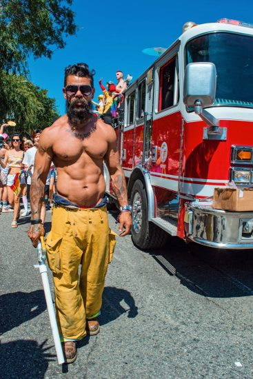 half naked man red fire department car blue sky at LA Pride in West Hollywood