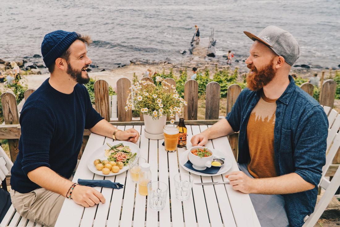 Gay Couple laughing and enjoying Lunch with View of Ransvik 'Sin of Molle' © Coupleofmen.com