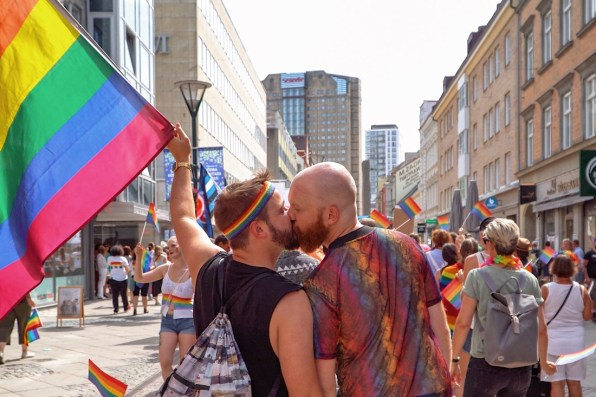Gay Pride Malmö 2019 Proudly waving the rainbow flag and giving each other a gay kiss during Malmö Pride 2019 © Coupleofmen.com