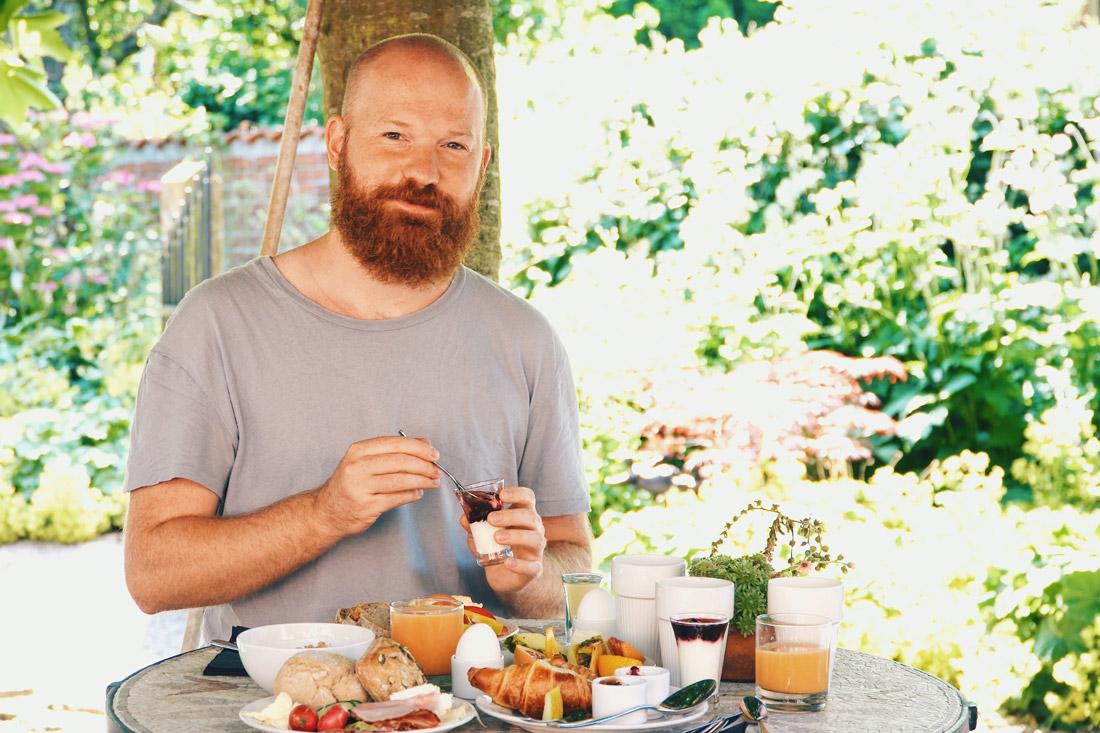Gay-owned Karnelund Krog & Rum Daan enjoying his breakfast in the garden of Karnelund Krog & Rum © Coupleofmen.com