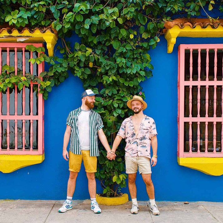 Gay Couple hand-in-hand in front of the colorful house facades in Cartagena © Coupleofmen.com
