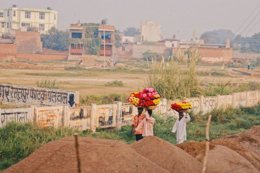Gay Reise Indien Men carrying beautiful flower arrangements along the train tracks © Coupleofmen.com