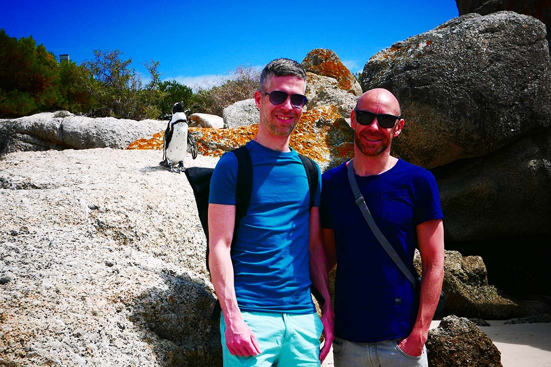 A penguin and the gay couple Gerson & Phil at Boulders Beach in South Africa