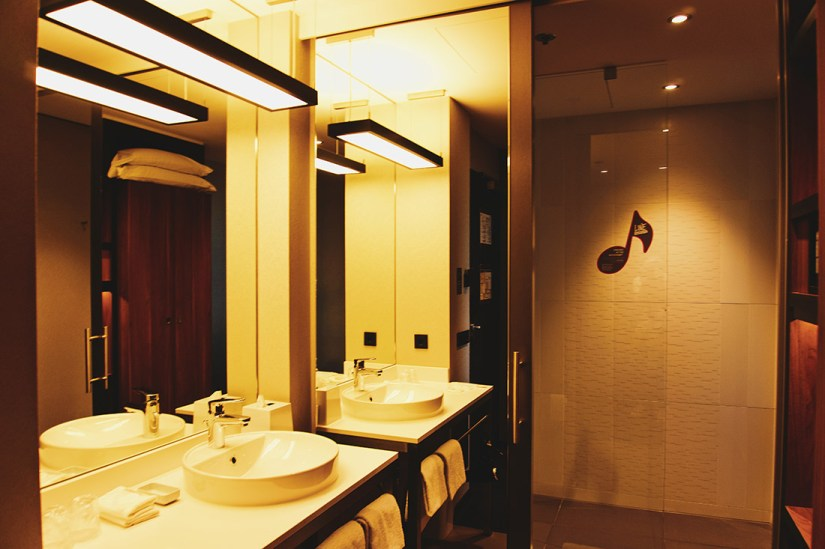 Spacious warm illuminated bathroom with a shower, hairdryer, an oval sink and included amenities © Coupleofmen.com