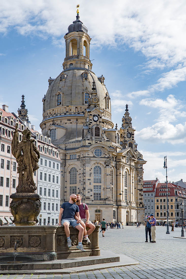 Dresden Gay City Trip Karl and Daan sitting by a fountain on Neumarkt in front of the Frauenkirche, Dresden-Altstadt © Coupleofmen.com
