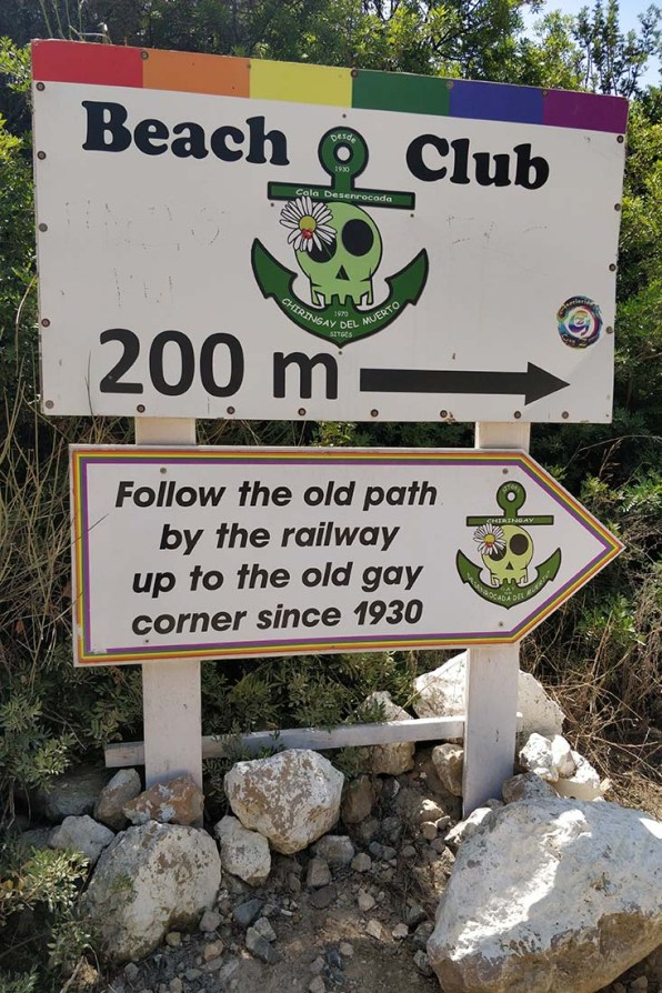 Colorful signs along the rails to Sitges Gay Beach Playa del Hombre Muerto