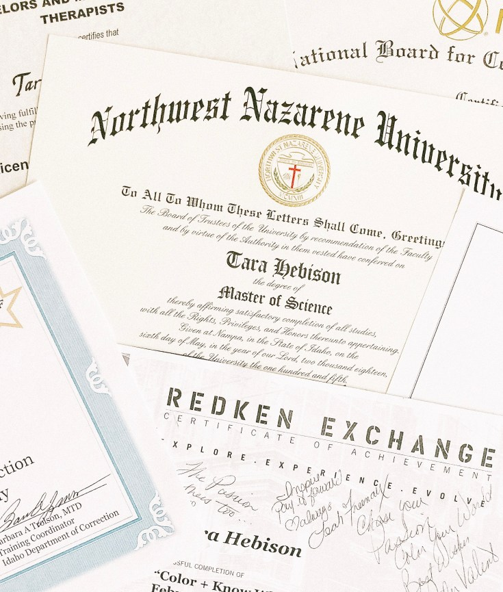 Degrees and certificates in a pile on the table taken by courageously.u