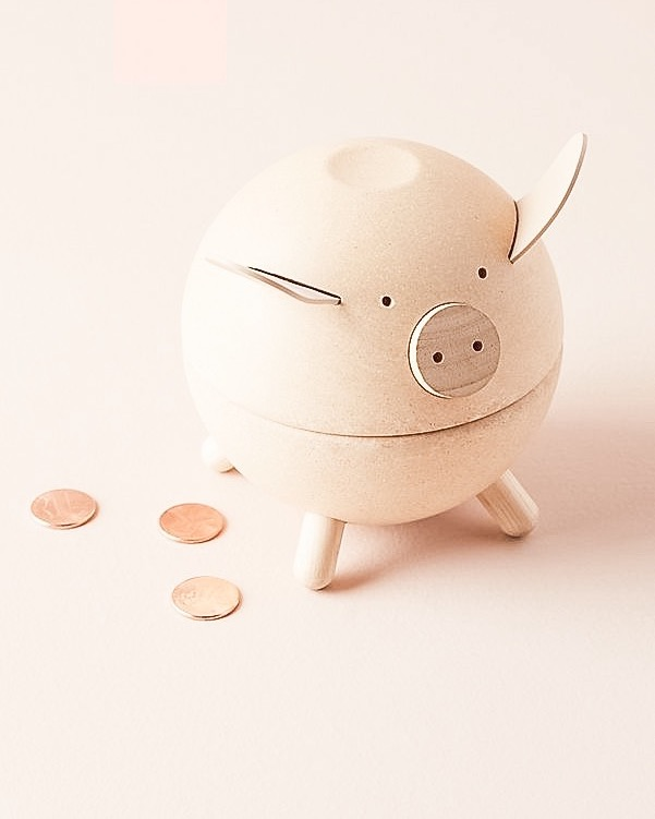 Anthropologie pink piggy bank with change laying around it