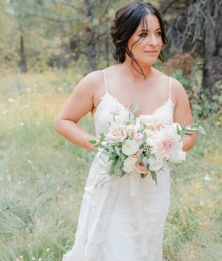 Bride on her wedding day in Donnelly, Idaho holding her bouquet