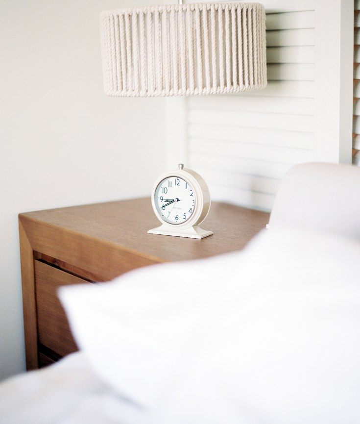Picture of a white alarm clock next to a cozy bed