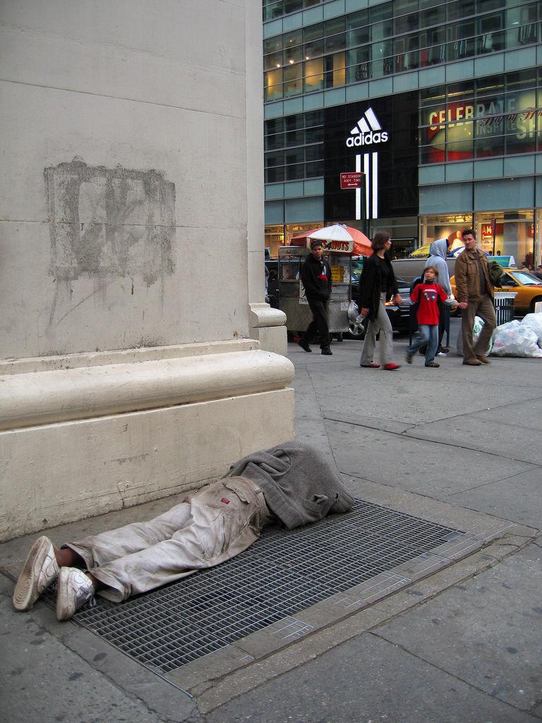 Contraste entre un sans-abris et le tourisme chic sur Broadway à New-York-City.