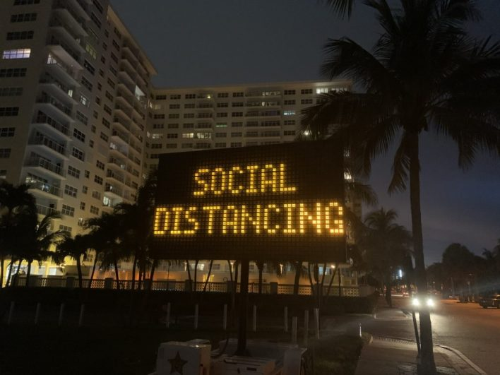 Panneau lumineux demandant la distanciation sociale face à la plage de Pompano Beach en Floride