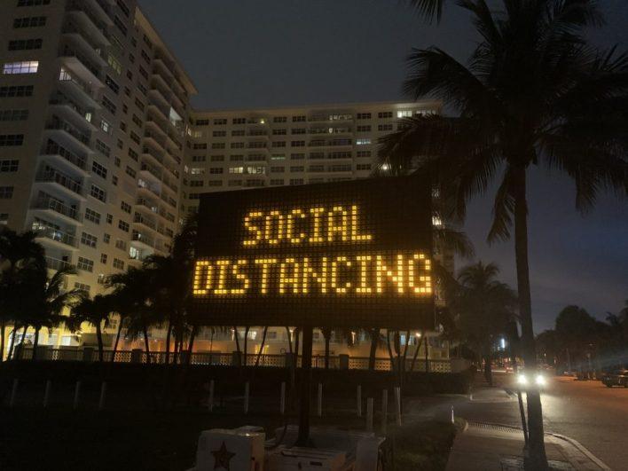 Panneau lumineux demandant la distanciation sociale face à la plage de Pompano Beach en Floride