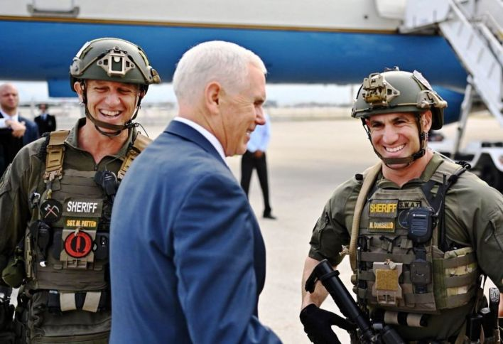 """Le vice-président Mike Pence salué par un membre des SWAT du comté de Browardtarborant un patch """"Q""""."""