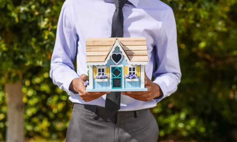 person holding a miniature house