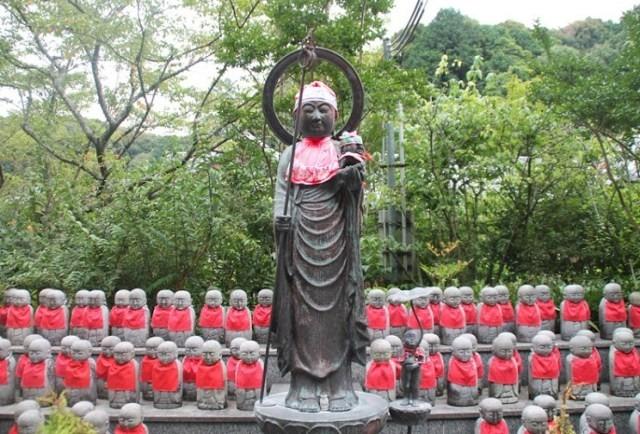 Statue du Bodhisattva Jizo, entouré de nombreuses autres statues mignones de Jizo