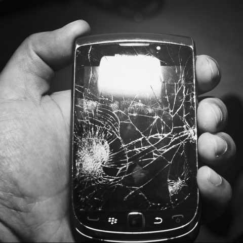 A hand holding a cell phone with a cracked screen