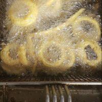 Onion rings frying in a fryer