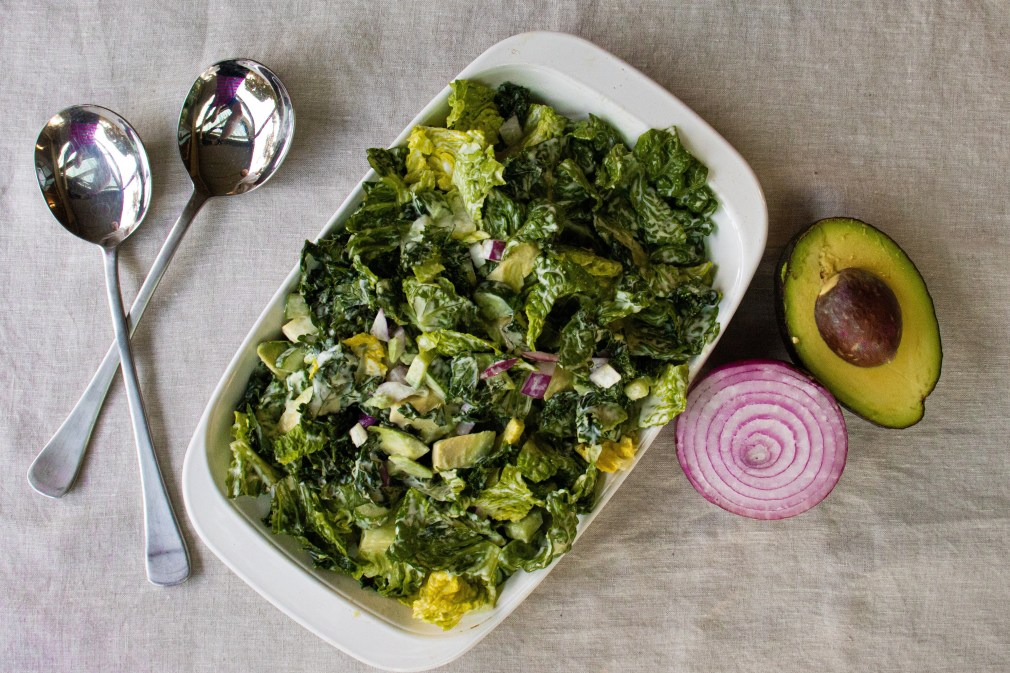 Kale salad pictured with avocado and red onion