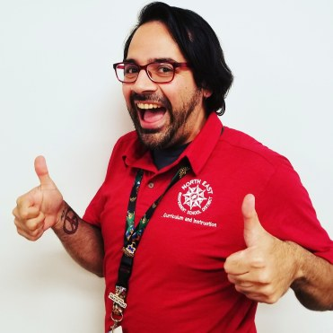 headshot of heath lopez in a red shirt, giving 2 thumbs up
