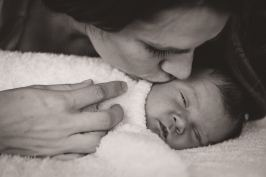 Newborn snuggles and kisses with mom captured by Courtney Liske Photography